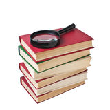 Stack of books and magnifying glass Stock Photo