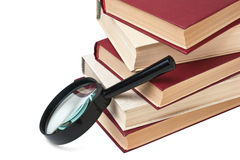 Stack of books and magnifying glass Royalty Free Stock Image