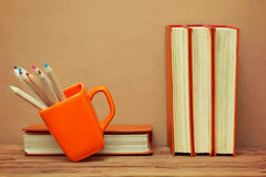 Stack of books and mug with colored pencils Stock Photography