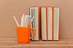 Stack of books and mug with colored pencils Royalty Free Stock Photos