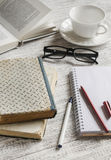 A stack of books, notebook and glasses , coffee cup on white wooden table. Stock Image