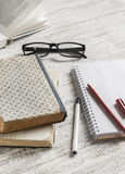 Stack of books, notebook and glasses on white wooden table. Stock Photography