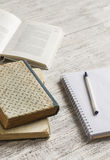 Stack of books, notebook  on white wooden table. Stock Photos