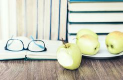 Stack of books, open book, glasses and green apples, background for education learning concept stock photos