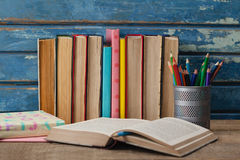 Stack of books, open book and pen holder. Against blue wooden background Stock Photo