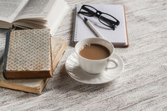 A stack of books, open  clean notepad, glasses and a cup of cocoa on a white wooden table. Royalty Free Stock Photo