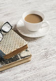 A stack of books, open  clean notepad, glasses and a cup of cocoa on a white wooden table. Royalty Free Stock Photography
