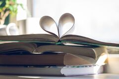 Stack of books with open one at the top. Heart of pages on background of open window. Love to read concept