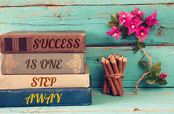 Stack of books over wooden table and motivational phrase. Success is one step away Royalty Free Stock Photo