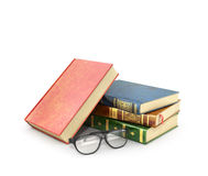Stack of books with a pair of eyeglasses. Stock Images
