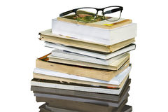 Stack of books. With a pair of glasse on a white background with path included Royalty Free Stock Photos
