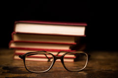 Stack of books with a pair of glasses Stock Photos