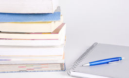 Stack of books, pen and notebook. Stack of many books on the white background Royalty Free Stock Photography