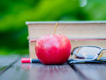 Stack of books and pencil. Stack of books, pencil, glasses and red apple on wooden table Stock Photo