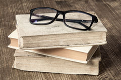 Stack of books with reading glasses Stock Images