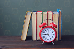 A stack of books and red alarm clock on the table. Stock Photo