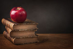 Stack of books and red apple. On wooden table Royalty Free Stock Image