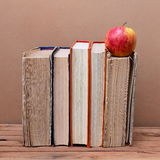 Stack of books and red apple on wooden table Royalty Free Stock Image