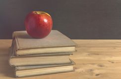 Stack of books and red apple on wooden table Royalty Free Stock Photography