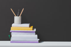 Stack of books and stationery in glass with black background Royalty Free Stock Photography