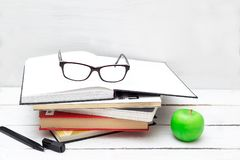 Stack of books for study and an apple on a white background Royalty Free Stock Photography