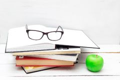 Stack of books for study and a green apple on a white background Royalty Free Stock Photography