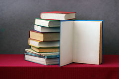 Stack of books on the table, one book opened. Royalty Free Stock Photo