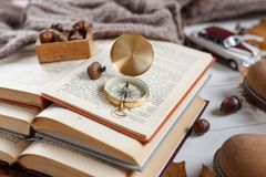 Stack of books on the table. Opened book with curled leaves and compass laying on top. Adventure tales Stock Image