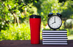 A stack of books, a thermo mug and an alarm clock. School concept. Work and education. Copy space Royalty Free Stock Photo