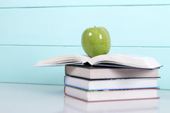 Stack of books on a turquoise background. And green apple. love of reading royalty free stock photo