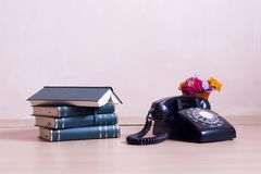 Stack of books with vintage telephone and flowers Stock Images