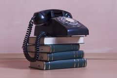 Stack of books with vintage telephone on top Stock Photos
