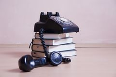 Stack of books with vintage telephone on top Royalty Free Stock Photography