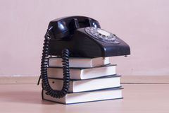 Stack of books with vintage telephone on top Royalty Free Stock Photo