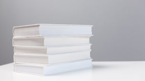Stack of books on a white desk Stock Images