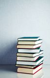 Stack of books on white reflective surface Royalty Free Stock Images