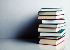 Stack of books on white reflective surface. Stack of red, green and black books on white reflective surface stock photos