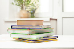 A stack of books on a white table. Stack of colored books in the background of wild flowers on the windowsill royalty free stock image