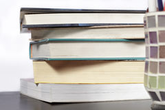 Stack of books on a wooden desk and white background Royalty Free Stock Photo