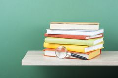Stack of books and magnifying glass on wooden shelf. Education background. Back to school. Copy space for text.