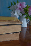 Stack of books on a wooden table, hibiscus. Stack of books on a wooden table on a background of Hibiscus bouquet, Rose Mallow, Shoe Flower, Roselle, China Rose Stock Images