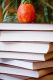 Stack of books on wooden table for reading with red delicious ap Royalty Free Stock Photo