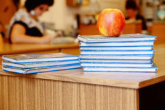 Stack of books on wooden table for reading with red delicious ap Royalty Free Stock Images