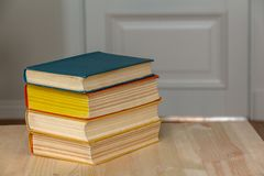 A stack of books on a wooden table stock photos