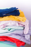 Stack of bright female trousers. Folded colorful pants and jeans.  Close up Stock Image