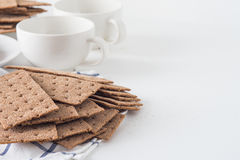 Stack of brown rye crispy bread Swedish crackers with two cups and piece of cloth on white background with space for text Royalty Free Stock Photography