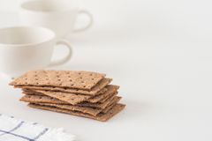 Stack of brown rye crispy bread Swedish crackers with two cups and piece of cloth on white background with space for text Stock Images