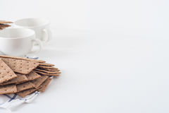 Stack of brown rye crispy bread Swedish crackers with two cups and piece of cloth on white background with space for text Royalty Free Stock Images