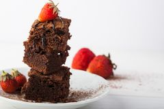 Stack of brownies decorated with strawberries on white plate on white background. stock photography