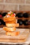 Stack of bruschetta with wine rack in background Royalty Free Stock Photo